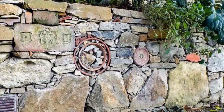 Kunst: Natursteinmauer mit Upcycling-Elementen