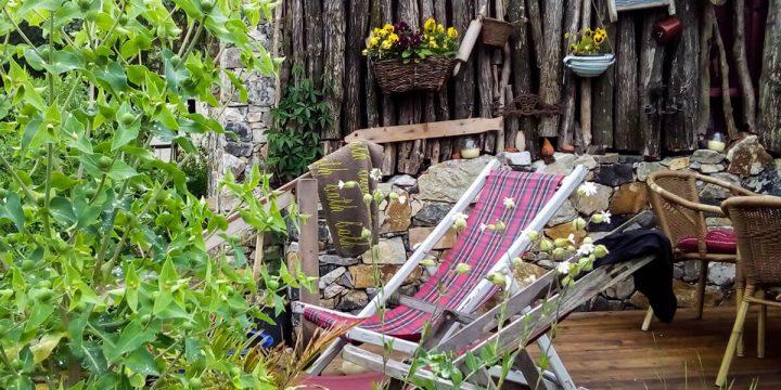 Holz: Sitzplatz vor Wand aus Naturstämmen mit Deko-Elementen