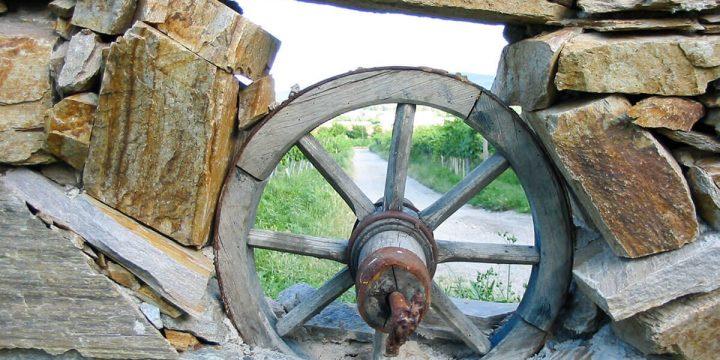 Kunst: Natursteinmauer mit Wagenrad-Fenster
